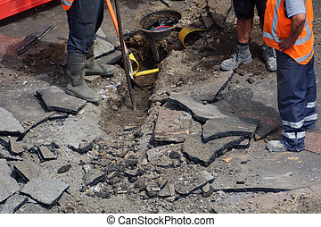 Road workers digging with shovel