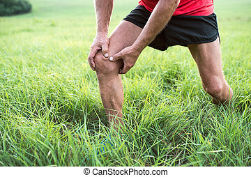 Unrecognizable runner in green field. Man with injured knee.