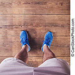 Unrecognizable runner - Legs of a runner on a wooden floor ...