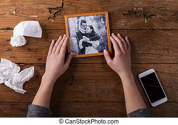 Unrecognizable sad woman holding broken picture of couple in...