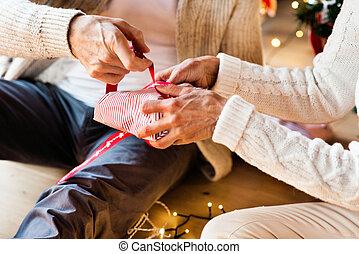 Unrecognizable senior couple wrapping Christmas gifts together.