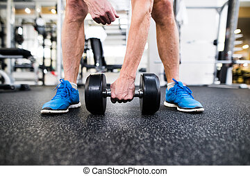 Unrecognizable senior man in gym working out with weights