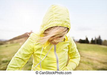 Unrecognizable senior runner outside on green hills.