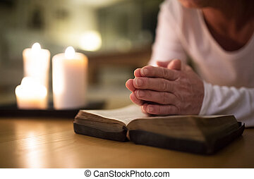 Unrecognizable senior woman praying, hands clasped together...