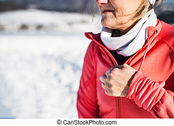 Unrecognizable senior woman runner resting in winter nature.