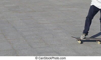Unrecognizable Skater doing trick kickflip on flat, close-up view in slowmotion