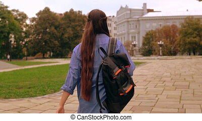 unrecognizable student strolling - back view young woman...