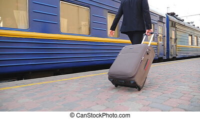 Unrecognizable successful businessman in black formal suit walking along platform and pulling suitcase on wheels. Young confident man with his luggage strolling near passing train. Slow mo Back view