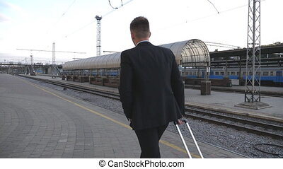 Unrecognizable successful businessman in suit walking through railway station and pulling suitcase on wheels. Camera follow to young man with his luggage going to business trip. Slow motion Back view