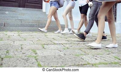 Unrecognizable teenage students walking to university. -...