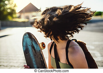Unrecognizable teenager girl with skateboard outdoors in city, having fun.