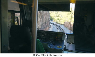 Unrecognizable train driver drives electrical train among mountain road. Point of view from driver cabin to railway tracks. Rear back view POV Slow motion Close up.