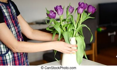 Unrecognizable woman arranging flower at home.