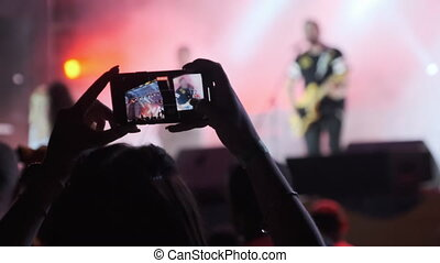 Unrecognizable Woman Hands Silhouette Recording Video of Live Music Concert with Smartphone. Shooting video on smartphone at rock concert. Crowd of people at music festival. Making video near stage.