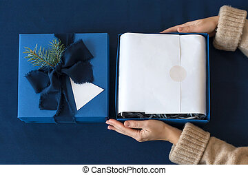Unrecognizable woman holding and unpacking gift in blue box...