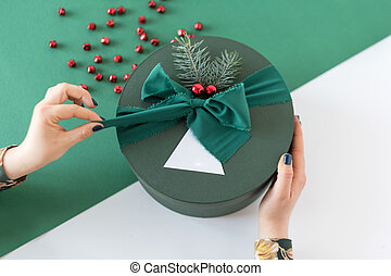 Unrecognizable woman holding and unpacking gift in green box...