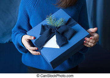 Unrecognizable woman holding Christmas gift in blue box with...