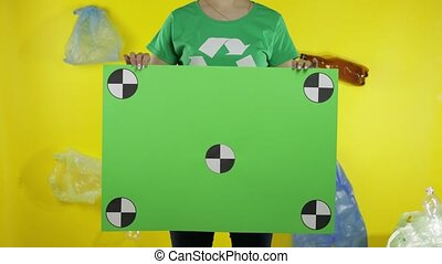 Unrecognizable woman volunteer in t-shirt with recycle logo holding protesting chroma key poster with tracking points. Background with cellophane bags, bottles. Environment trash plastic pollution