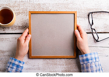 Unrecognizable woman holding empty picture frame, studio shot.