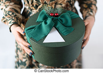 Unrecognizable woman holding gift in green box. Happy winter...
