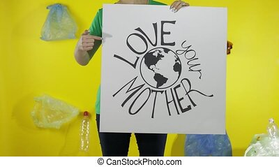 Unrecognizable woman holding protesting poster Love Your Mother Earth. Environment plastic pollution