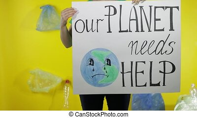 Unrecognizable woman activist in t-shirt with recycle logo holding protesting message poster Our Planet Needs Help. Background with cellophane bags, bottles. Environment trash plastic pollution