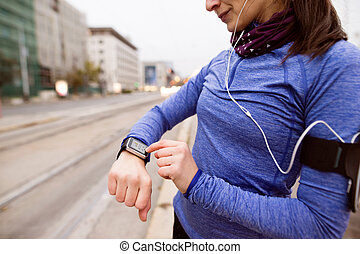 Unrecognizable woman in blue sweatshirt running in the city...