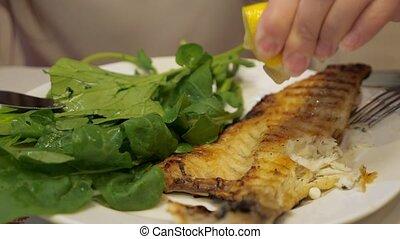 Unrecognizable woman is pouring fish with lemon juice,...