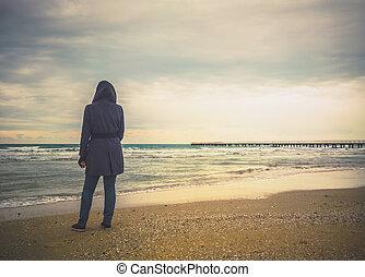 unrecognizable woman looks at winter sea
