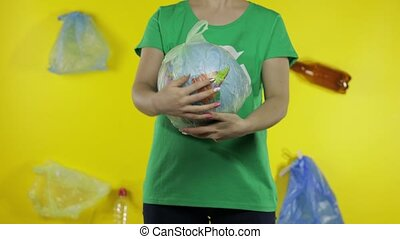 Unrecognizable woman girl volunteer in t-shirt with recycle logo makes Earth globe free from plastic package. Yellow background with bags, bottles. Save planet ecology environment. Nature pollution