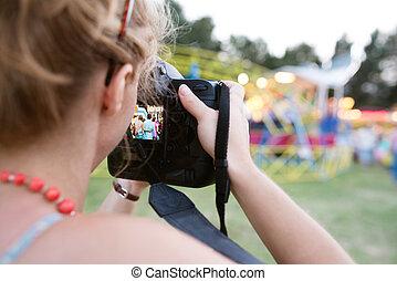 Unrecognizable woman photographing senior couple, fun fair