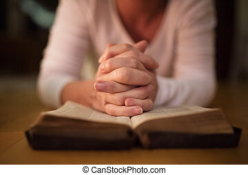 Unrecognizable woman praying with hands clasped together on her Bible. Close up.