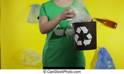 Unrecognizable woman girl volunteer in t-shirt with recycle logo put cellophane package in bin dump. Yellow background with bags, bottles. Save ecology environment. Plastic trash nature pollution