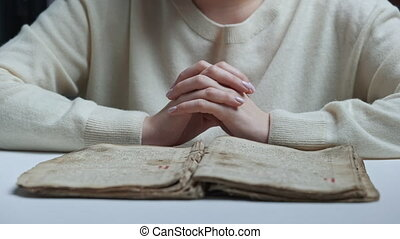 Unrecognizable woman reading old ancient book - Holy Bible and praying. Christian studying scripture. Learning, gratitude, religion concept. High quality 4k footage