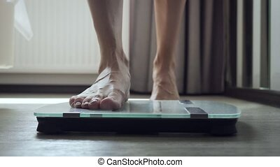 Unrecognizable woman stands on floor scale in the bedroom....
