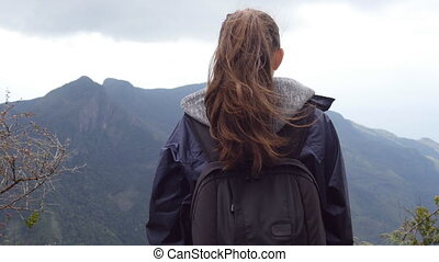 Unrecognizable woman tourist standing on the edge of beautiful canyon and enjoying landscapes. Young female hiker in raincoat with backpack reaching up top of mountain and raised hands. Rear back view