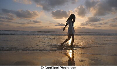 Unrecognizable woman walking on the ocean beach and spraying water with her feet. Young beautiful girl enjoying life and having fun at sea shore. Summer vacation. Sunset at background. Slow motion