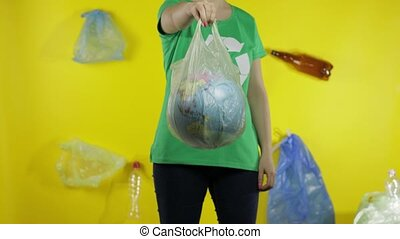 Unrecognizable woman girl activist in t-shirt with recycle logo with Earth globe in cellophane package. Yellow background with bags, bottles. Save ecology environment. Plastic trash nature pollution
