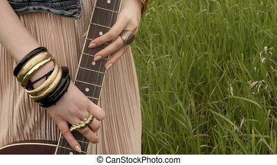 Unrecognizable woman with guitar on field