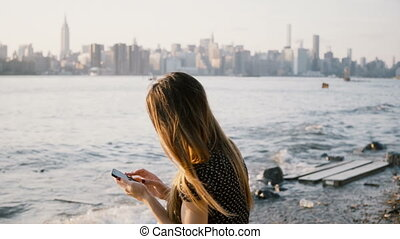 Unrecognizable woman with long hair using smartphone app at river beach with New York city skyline view on sunset 4K.