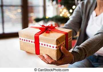 Unrecognizable senior woman sitting on the floor in front of illuminated Christmas tree inside her house giving present.