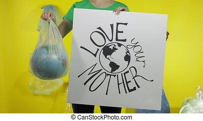 Unrecognizable woman with protesting poster and Earth globe in plastic package. Ecology pollution