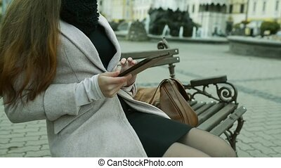 Unrecognizable woman working on tablet on bench in old town