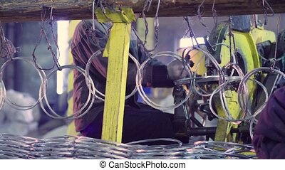 Unrecognizable workers producing metal net in the factory -...