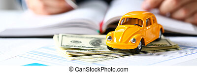 Unrecognizable yellow car on selling documents and pack of...