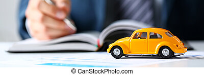Unrecognizable yellow toy car on selling documents closeup...