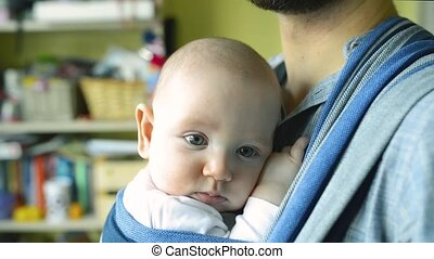 Unrecognizable young father with his son in sling - Close up...