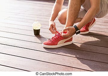Unrecognizable young runner tying his shoelaces outdoors.