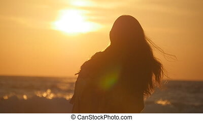 Unrecognizable young traveler woman going on ocean shore at sunrise. Young female tourist with backpack walking along sea beach at sunset. Girl hiker stepping during summer vacation. Slow motion