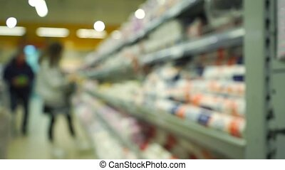 Unrecognizable young woman chooses goods in supermarket. Bokeh slow motion video